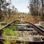 burnt railway bridge on the Boyne Burnett Inland Rail Trail with only the steel rail left hanging in the air