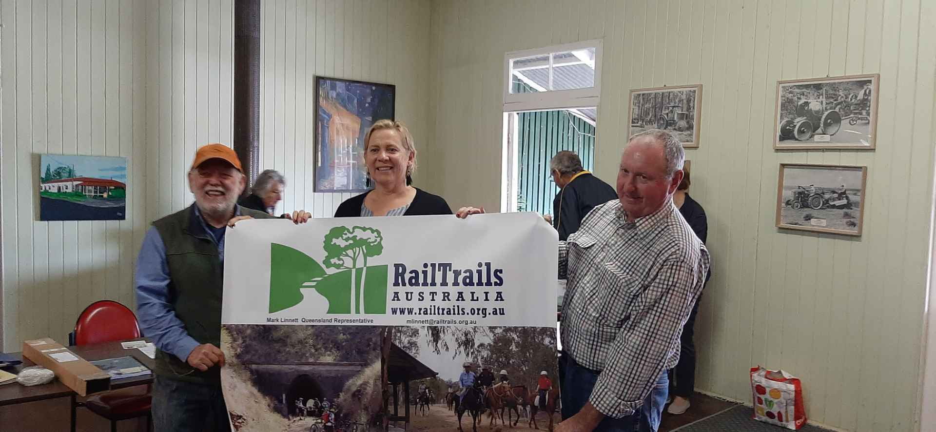 Councillor Desley O'Grady, Mick Colyer, Mike Goebel holding up a Rail Trail banner