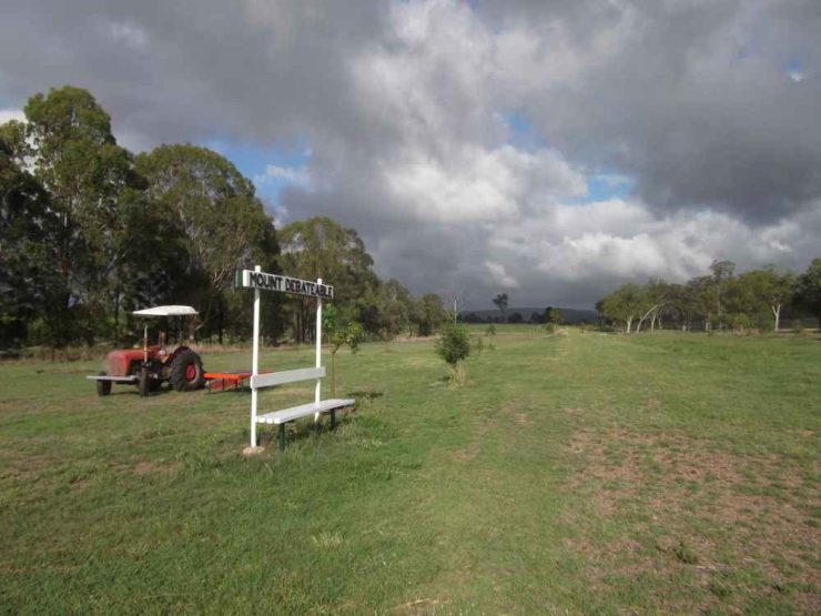 Mount Debatable siding, green mown grass and tractor in country side