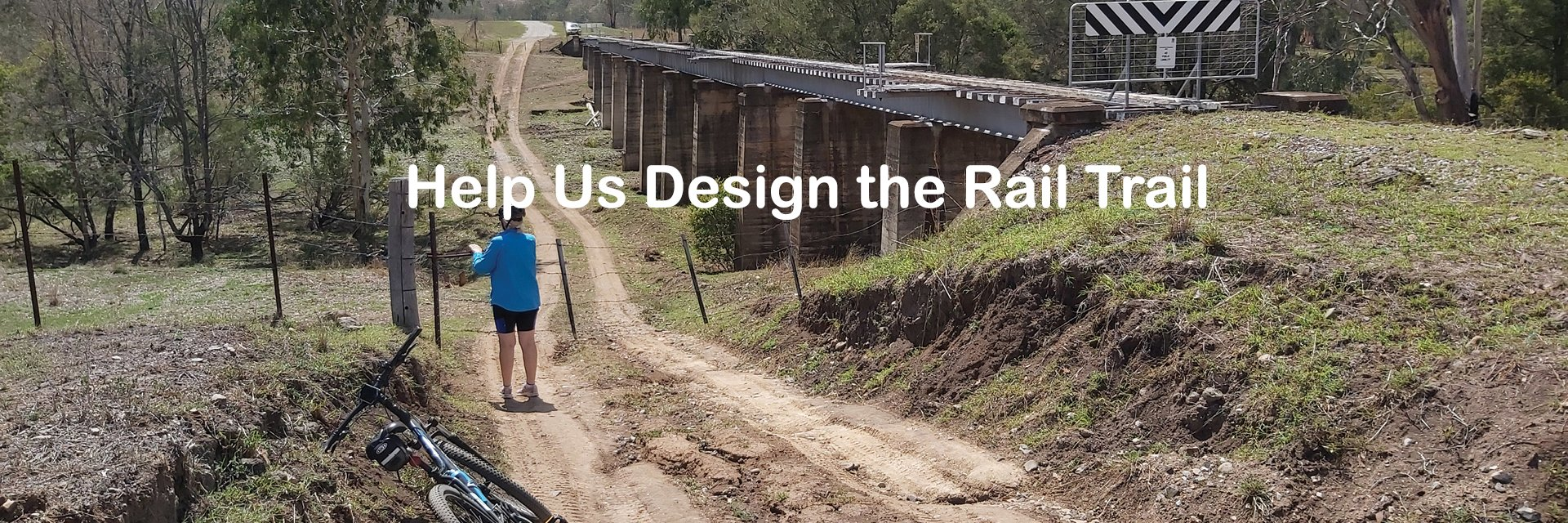 cyclist opening gate near railway bridge with writing help us design the rail trail